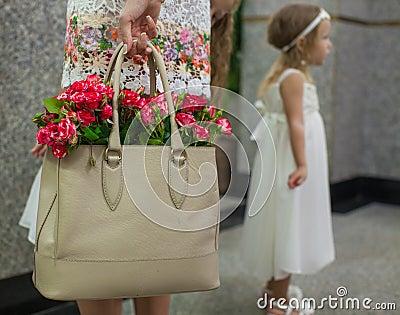 Kleine rode charmante rozen in de zak van maniervrouwen binnen