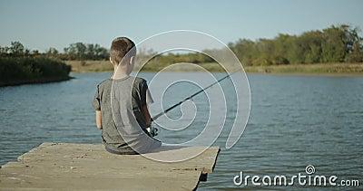 Kleine zoontvissers vangen een vis op een staaf op het meer Buiten stock footage