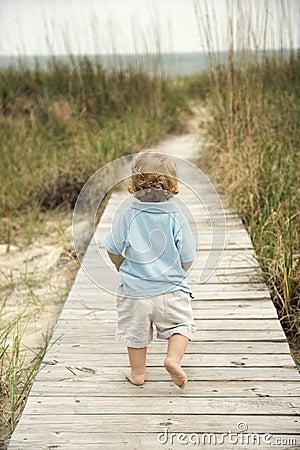 Kleiner Junge, der hinunter Strandgehweg geht.