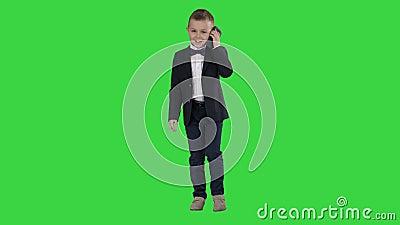 Kleiner Junge in einem Kostüm, der einen Anruf macht, während er auf einem grünen Bildschirm läuft, Chroma-Taste stock video