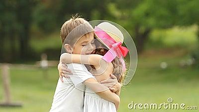 Kleiner Junge umarmt leicht das Mädchen, sind sie glücklich und sorglos Langsame Bewegung stock video