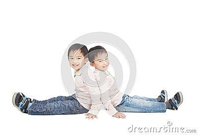 Kleiner Junge zwei, der auf dem Boden sitzt