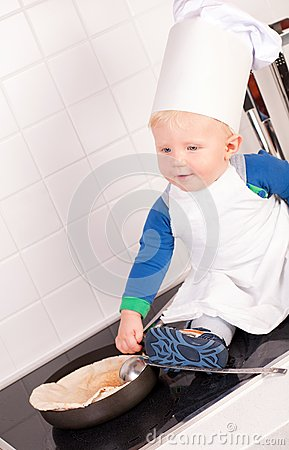 Kleiner Schätzchenchef im Kochhut, der Pfannkuchen bildet