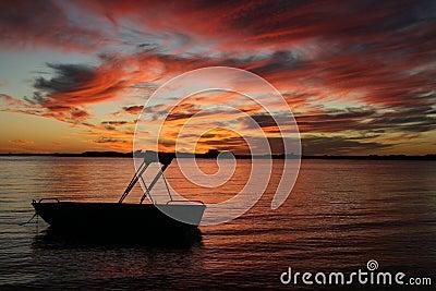 Kleines Boot im Wassersonnenuntergang