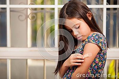 Kleines Mädchen, das an ein Pflaster setzt