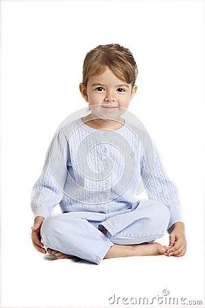 Kleines Mädchen, das queresmit beinen versehenes sitzt