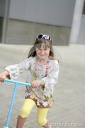 Kleines Mädchen des Brunette mit Roller in der Stadt
