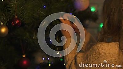 Kleines Mädchen hängendes Weihnachtsbaumspielzeug, Dekoration für Feiertage, Nahaufnahme stock footage