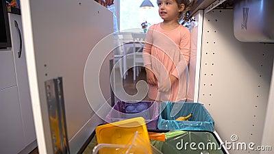 Kleines Mädchen lässt den Abfall in Küchen-Wiederverwertungs-Behälter fallen stock video footage