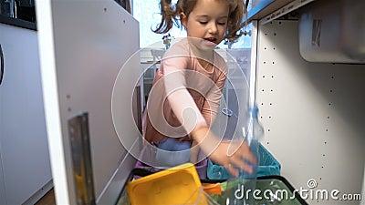 Kleines Mädchen lässt den Abfall in Küchen-Wiederverwertungs-Behälter fallen Langsame Bewegung stock footage