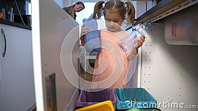 Kleines Mädchen lässt den Abfall in Küchen-Wiederverwertungs-Behälter fallen Langsame Bewegung transportwagen stock video footage