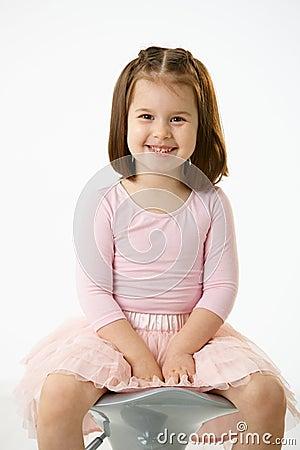 Kleines Mädchen, das auf Stuhl sitzt