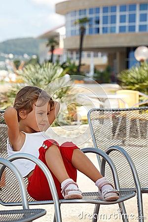 Kleines Mädchen, freier Sommertag, der im Lehnsessel sitzt
