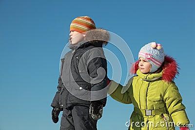 Kleines Mädchen und Junge, die am Schnee steht