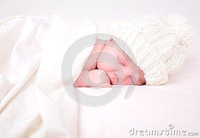 Kleines neugeborenes Schätzchen, das auf Weiß mit Decke schläft