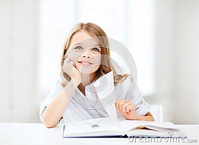 Kleines Studentenmädchen, das in der Schule studiert