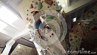 Klettersteiger Young Woman Rock Klettersteig Inside Klettern schlanke schöne Frauenübung an der Innenwand stock footage