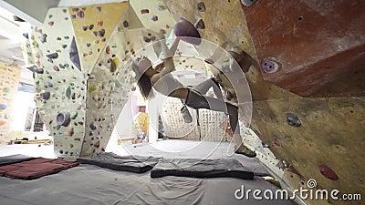 Klettersteiger Young Woman Rock Klettersteig Inside Klettern schlanke schöne Frauenübung an der Innenwand stock video footage
