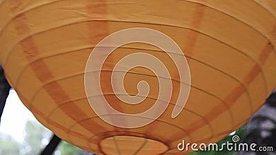 Kleurrijk traditioneel oranje papieren lantaarn dat buiten hangt, feestelijke decoraties die in de wind zwaaien stock video
