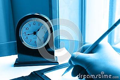 Klok en het schrijven hand op nota
