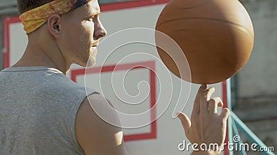 Knap kerel spinnend basketbal op zijn vinger, die professionalisme, sport tonen stock videobeelden