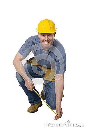 Kneeling construction worker smiles