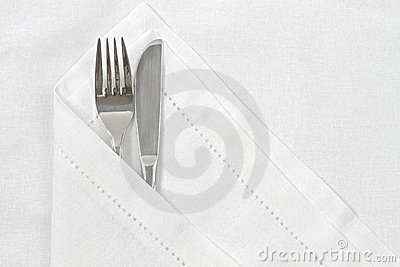 Knife and fork with white linen serviette