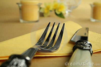 Knife and fork on yellow tablecloth
