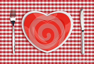 Knife, heart plate and fork on red tablecloth