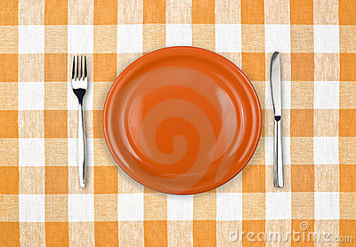 Knife, plate, fork on checked tablecloth