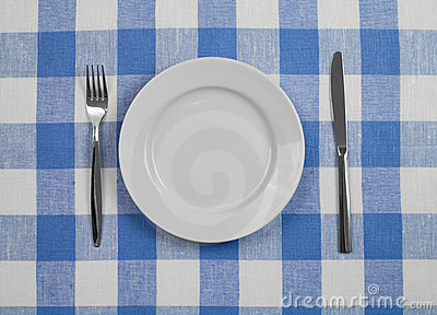 Knife, plate and fork checked tablecloth top view