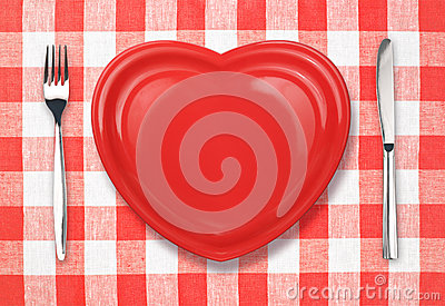 Knife, plate in heart shape and fork on tablecloth