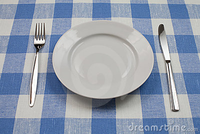 Knife, white plate and fork on blue tablecloth
