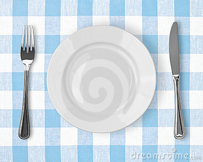 Knife, white plate and fork on checked tablecloth
