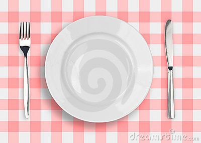 Knife, white plate and fork on checked  top view