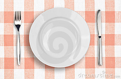 Knife, white plate and fork on pink tablecloth