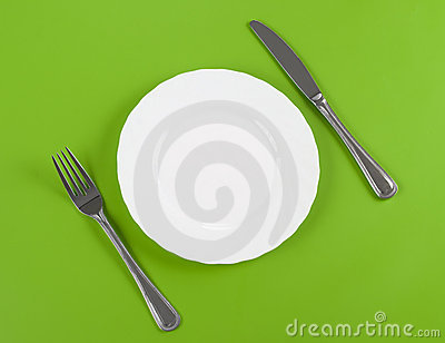 Knife, white round plate, fork on green top view