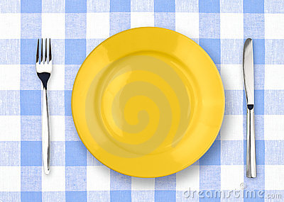 Knife, yellow plate and fork on checked tablecloth