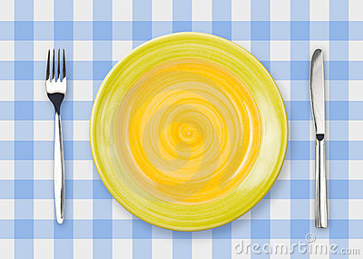 Knife, yellow plate and fork on checked top view