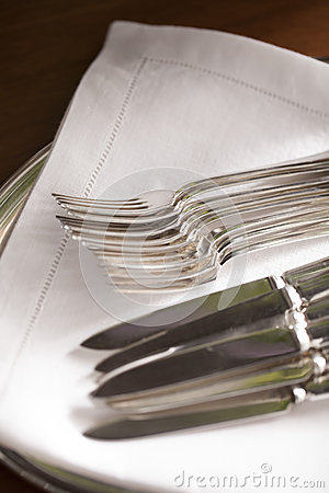 Knifes and forks on white napkin