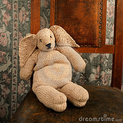 Knitted bunny sitting on an old chair square