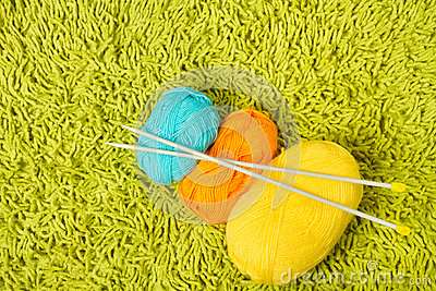 Knitting yarn balls and needles over green carpet
