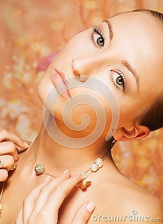 Kobiecy. Czułość. Portret Nakładająca kobieta z Złocistym Perłowym łańcuszkiem