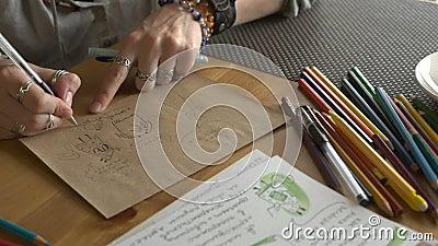 Kobieta artysta rysuje ilustracje dla children książki z ołówkami zbiory