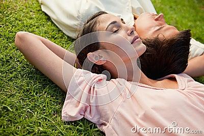 Kobieta i mężczyzna lying on the beach przewodzimy brać na swoje barki
