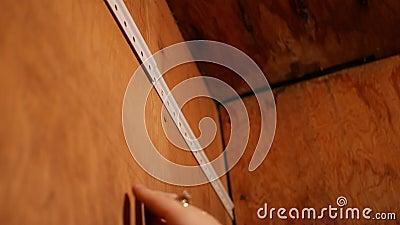Kobieta przygotowywa przybijać poparcie promień dla szafa magazynu półki zdjęcie wideo