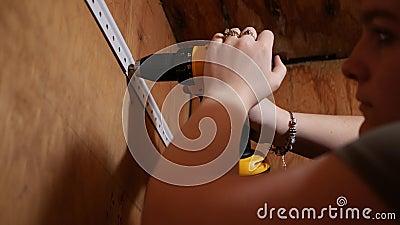 Kobieta używa elektrycznego śrubokrętu świder zakotwiczać poparcie promień zbiory