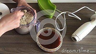Kobieta usuwa dekiel blender i miesza z łyżka siekającymi ziarnami dla robić halva i arachidami Obok zbiornika jest zdjęcie wideo
