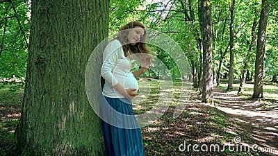 Kobieta w ciąży relaksuje blisko drzewnego bagażnika w parku w ninth miesiącu zbiory