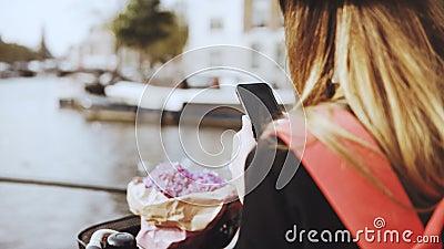 Kobieta z bicyklem bierze fotografie na rzeka moscie Dama z długie włosy i kwiatami dzieli fotografie z przyjaciółmi online 4K zbiory wideo